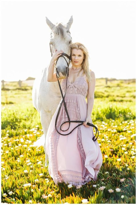 Woman in beautiful dress holding white horse