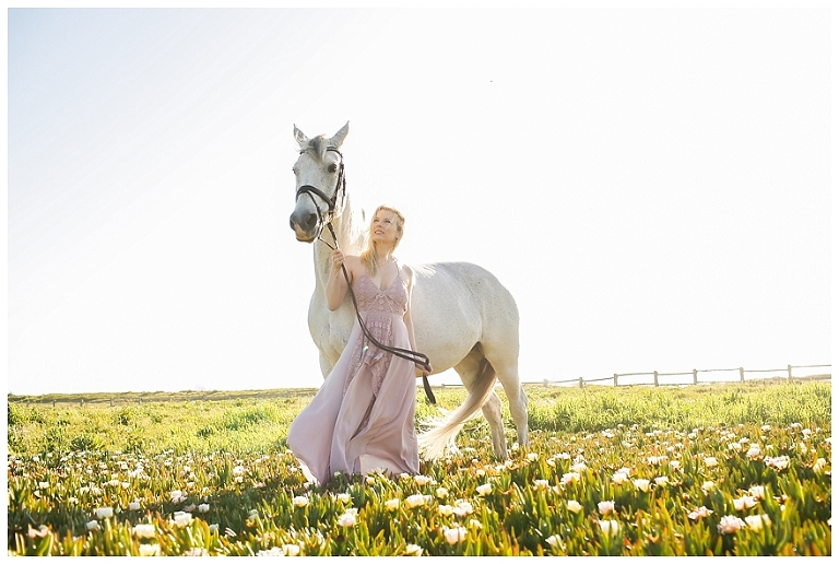 Woman in pink dress with white horse
